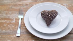Close up of heart shaped decoration on plate. Valentines day and romantic dinner concept - close up of wicker heart shaped decoration on set of dishes on wooden stock video footage