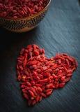Close-up of heart shaped dried goji berries on dark background stock photo