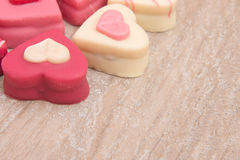 Close up of heart shaped petit fours cakes on a wooden background. Close up of heart shaped petit fours cakes seen the side on a wooden background Stock Photos