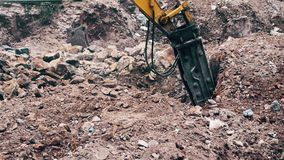 Close up of a heavy duty construction industry excavator machine crushing stones in a construction site. Close up of a large pneumatic hammer on an excavator stock video
