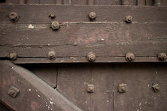 Close up of Heavy wooden door of a temple in Asia studded with b. Close up of a heavy wooden door of a temple in Asiastudded with bolts; crossbeams and slats Royalty Free Stock Photos