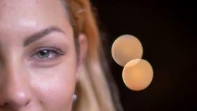Close-up helft-gezicht portret van volwassen aantrekkelijk blonde Kaukasisch wijfje die recht camera met bokehachtergrond bekijke stock footage