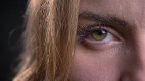 Close-up helft-gezicht portret van volwassen Kaukasisch vrouwelijk gezicht met linkeroog die recht camera bekijken stock video