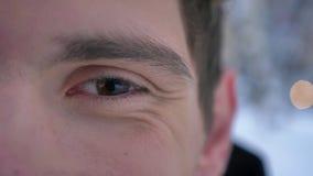 Close-up helft-gezicht spruit van jong aantrekkelijk Kaukasisch mannelijk gezicht met bruin oog die camera met gezichts glimlache stock videobeelden