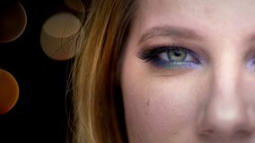 Close-up helft-gezicht spruit van jong mooi vrouwelijk gezicht met ogen die camera bekijken die met bokehlichten glimlachen op stock footage