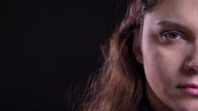 Close-up helft-gezicht spruit van volwassen vrouwelijk gezicht met donkerbruin haar en bruin oog die recht camera bekijken die bi stock video