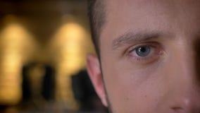 Close-up helft-gezicht voorspruit van volwassen Kaukasisch mannelijk oog die camera binnen met binnenland op de achtergrond bekij stock foto