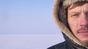 Close-up helft-portret van ontdekkingsreiziger op middelbare leeftijd in kap het letten calmly op in camera op de achtergrond van stock videobeelden