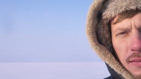 Close-up helft-portret van ontdekkingsreiziger op middelbare leeftijd in kap het letten smilingly op aan de zon op de achtergrond stock video