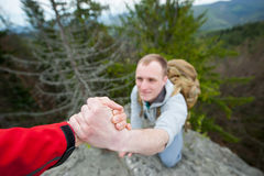 Close-up of helping hand, hiking help each other. Focus on hands. People teamwork climbing or hiking with motivation and inspiration. Wide angle lens Royalty Free Stock Photos