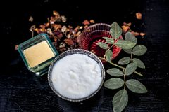 Close up of herbal and ayruvedic face pack of rose or Rosa or Rosaceae or gulab with its extracted rose water in a glass bowl. With gram flour and yogurt on stock photography