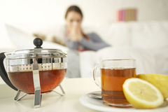 Close-up of herbal tea on a table with a mid adult woman sitting in the background stock photos