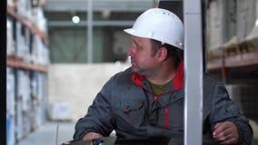 Close-up Het gezicht van de bestuurder van een vorkheftruck Een mens werkt in een logistiekpakhuis 4K langzame mo stock videobeelden