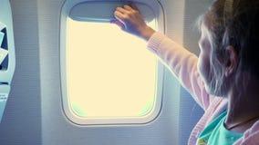 Close-up Het jong geitjemeisje heft het patrijspoortgordijn in de cabine van het vliegtuig op, van er glanst een helder licht Sch stock video