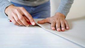 Close-up het mannelijke handen nieuw bended voorbereidingen treffen behangbroodje met kantoorbehoeftenmes op lijst binnen royalty-vrije stock afbeelding