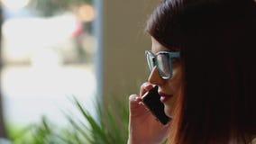 Close-up Het meisje selecteert het noodzakelijke contact in het telefoonboek van de mobiele telefoon en glimlacht het spreken aan stock video