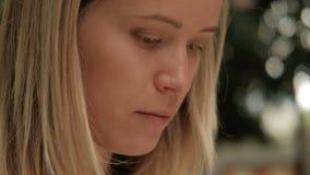 Close-up het schieten van het blonde van het vrouwengezicht trekt in openlucht, kijkt onderaan stock videobeelden
