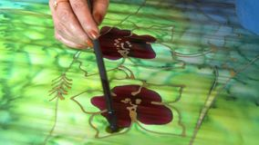 Batik Flower Painting, Kuala Lumpur, Malaysia. Close-up high angle still shot of an artist hand-painting a maroon flower pattern on a batik textile with a green stock video footage