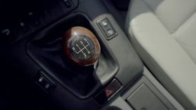 Close up high angle video shot of a manual car gear stick with the gearbox in a blurry background.  stock footage