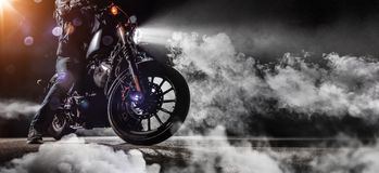 Close-up of high power motorcycle chopper with man rider at nigh Stock Photography