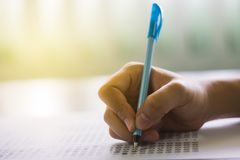 Close up of high school or university student holding a pen writing on answer sheet paper in examination room. College students an stock images