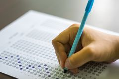 Close up of high school or university student holding a pen writing on answer sheet paper in examination room. College students an stock photo