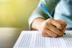 Close up of high school or university student holding a pen writing on answer sheet paper in examination room. College students an royalty free stock image