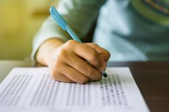 Close up of high school or university student holding a pen writing on answer sheet paper in examination room. College students an