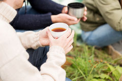 Close up of hikers drinking tea from cups at camp Stock Images