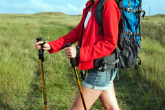 Close up of hiking young woman with backpack. And trekking poles on the mountain trail Royalty Free Stock Photo