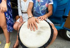 Close up of hippie friends playing tom-tom drum. Summer holidays, music, travel and people concept - close up of hippie friends having fun and playing tom-tom Royalty Free Stock Photo
