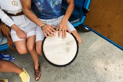 Close up of hippie friends playing tom-tom drum. Summer holidays, music, travel and people concept - close up of hippie friends having fun and playing tom-tom Royalty Free Stock Photography