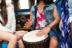 Close up of hippie friends playing tom-tom drum. Summer holidays, music, travel and people concept - close up of hippie friends having fun and playing tom-tom Royalty Free Stock Images
