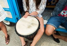 Close up of hippie woman playing tom-tom drum. Summer holidays, music, travel and people concept - close up of hippie woman with friends having fun and playing Stock Photos