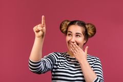 Close up of a hipster girl with funny hairstyle showing silence gesture isolated over pink background. Young funny teen girl cover the mouth and pointing finger stock photo