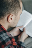 Close up Hipster man in red checkered shirt reading book and lie. S on the couch Stock Images