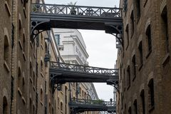 Close up of historic, renovated Butler`s Wharf warehouse building and iron bridges at Shad Thames, London.