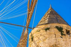 Ancient historical windmill on Mallorca, Spain. Close-up of historic wind mill with blue sunny sky on Majorca island Stock Photos