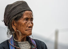 Close up of Hmong elderly woman against gray skies. Royalty Free Stock Photo