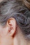 Close-up hogere vrouw die gehoorapparaat opnemen in haar oren royalty-vrije stock foto's