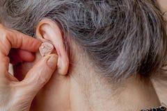 Close-up hogere vrouw die gehoorapparaat opnemen in haar oren royalty-vrije stock afbeeldingen
