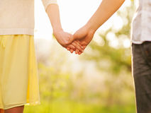Close-up Holding Hands. A young couple walking in the autumn park holding hands Royalty Free Stock Photography