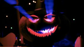 Close-up of holiday Halloween carved glowing pumpkin in the club stock video footage