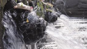 Close-up of holy spring water stream pouring into pool and traditional Balinese offerings Canang sari made of leaves and stock footage