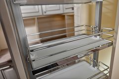 Close Up home interior. Kitchen - opened door with chrome furniture shelf. Wood and Chrome Material, Modern Design.  royalty free stock image