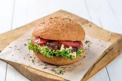Close-up of home made burger on wooden board royalty free stock photography