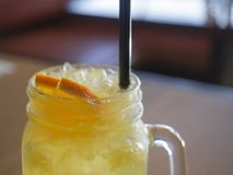Close up home made lemon orange lemonadesoft drink in pint glass. With straw, selective focus stock photography