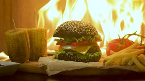 Close-up of home made tasty burger with french fries and fire flames. stock video footage
