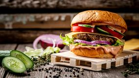 Close-up of home made tasty burger with meat cutlet and cheese and fresh vegetables on wooden vintage table. Food recipe photo, royalty free stock photos