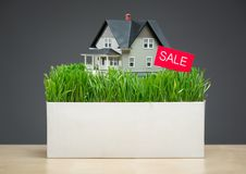 Close up of home model with grass and sale tablet. Close up of home model with green grass and sale tablet on grey background. Concept of real estate and sales royalty free stock photography